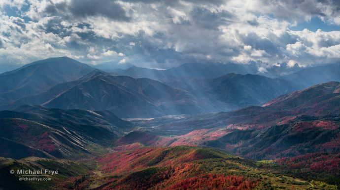 Sunbeams, mountains, and autumn maples, UT, USA