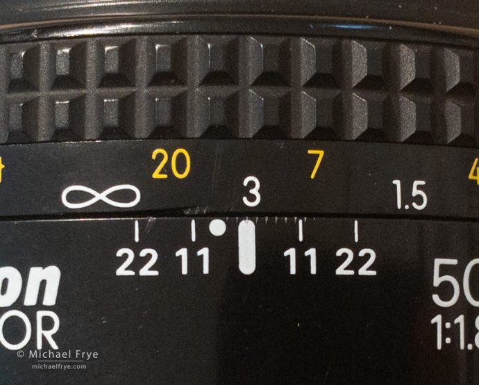 If the closest object to the camera is 7 feet away, and the farthest object is 20 feet away, then I focus halfway between those two marks on the lens.